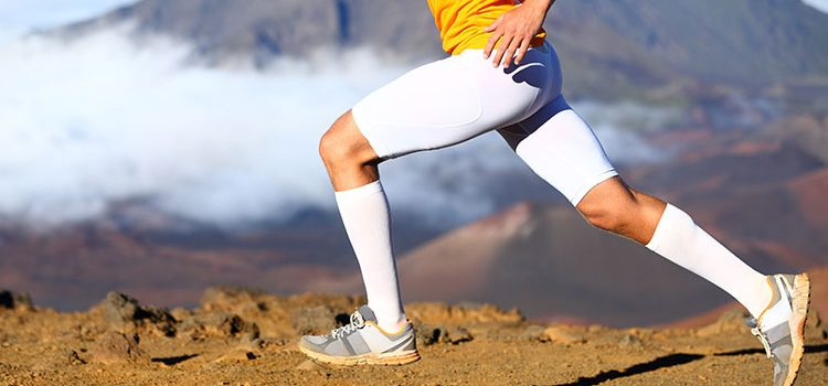 Runner with compression clothing (socks) trying to reduce muscle soreness prevent injuries and improve performance despite scientific evidence showing inconclusive results